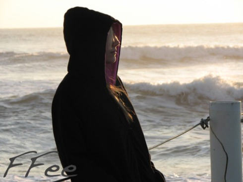astrid at the beach wearing the black angel hoody